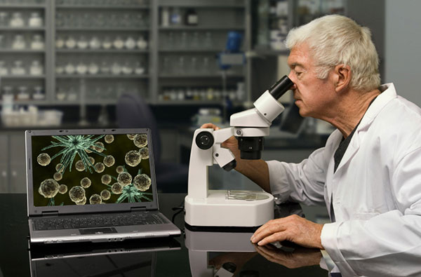 Person Looking Through Microscope